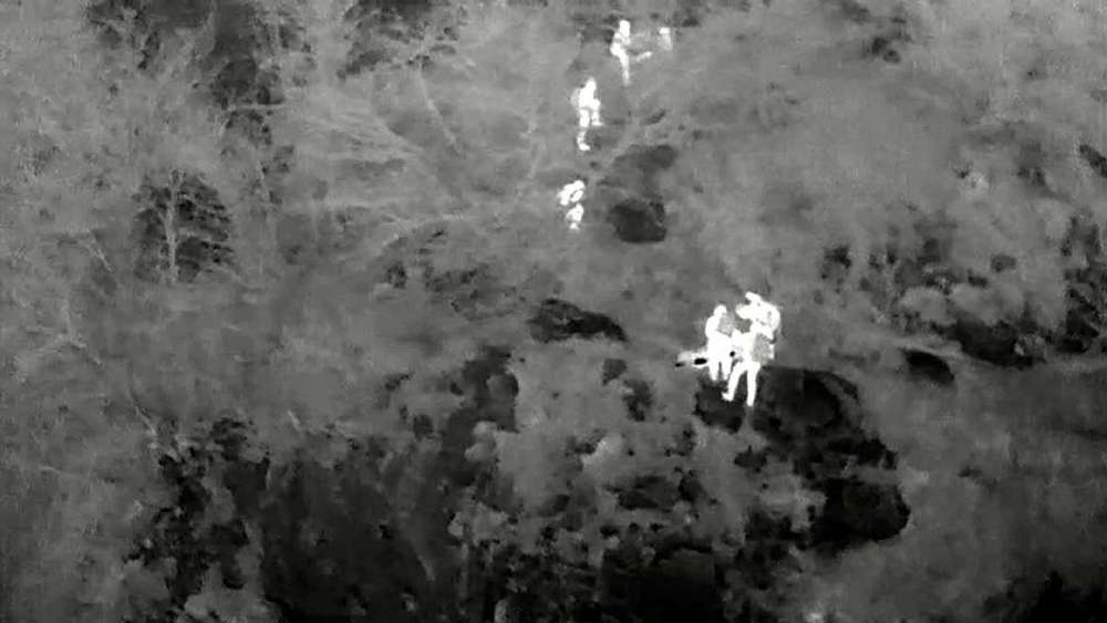 "This airborne thermal image of a search and rescue training exercise shows how human beings stand out a luminous figures against the background in a wilderness setting. Notice that the camera is using a ""white-hot"" color palette, so that the warmest object in the field of view is displayed as white, the coldest is black, and objects at intermediate temperatures are displayed as shades of gray."